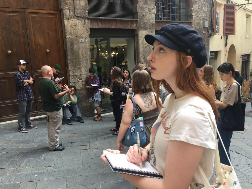 Art students sketch during a walking tour of medieval Siena with GEO instructor Piergiacomo Petrioli
